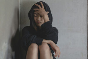 Depressed And Hopeless Teenage Girl Sitting Alone After Using Dr